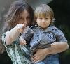 Mutter hält Sohn im Arm und zeigt auf Dich.